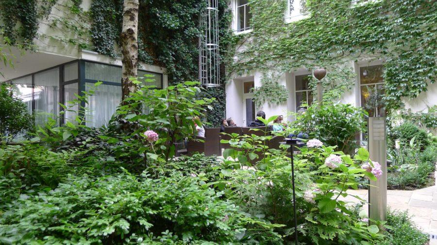 Innenhof mit bodengebundener Fassade mit Selbstklimmern